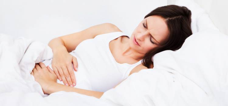 Woman with stomach ache lying on bed